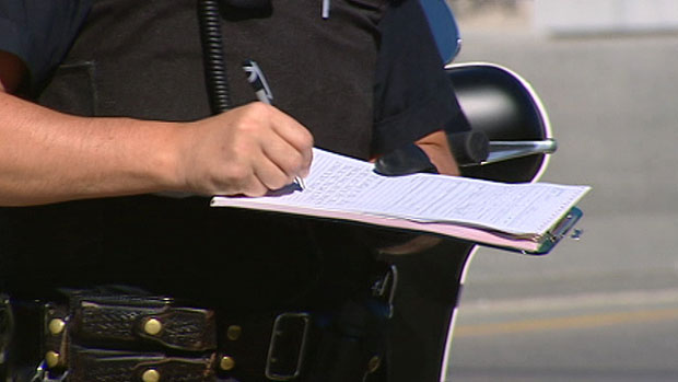 Police Officer Writing a Highway Traffic Act Violation Certificate
